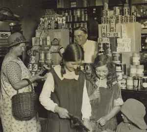 Three children and a lady at the counter of the Enham village shop, 1930