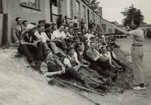Group of disabled ex-servicemen sitting outside one of the workshops on their lunch break at Enham Village Centre, 1935